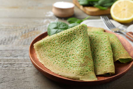Delicious spinach crepes served on wooden table