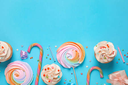 Flat lay composition with cupcakes on light blue background. Space for text Фото со стока
