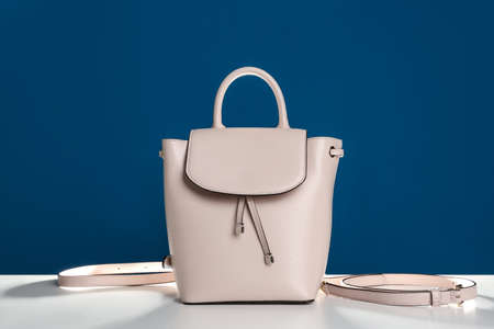 Stylish womans bag on white table against blue background