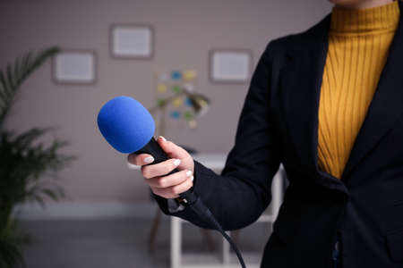 Professional journalist with modern microphone in room, closeup Stock Photo