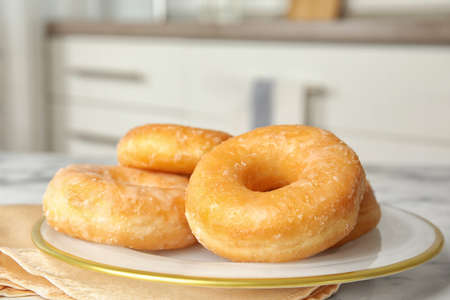 Delicious glazed donuts on marble table, closeup Фото со стока