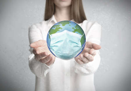 Woman holding Earth with medical mask on light background, closeup. Concept of coronavirus outbreak