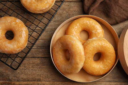 Delicious donuts in box on wooden table, flat lay