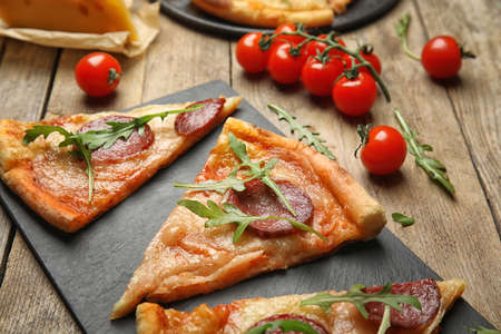 Tasty pepperoni pizza with arugula on wooden table