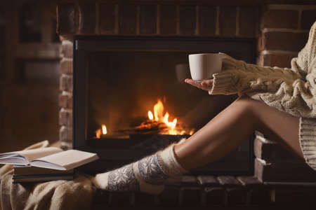 Woman in knitted socks holding hot drink near fireplace at home, closeup. Winter vacation Imagens
