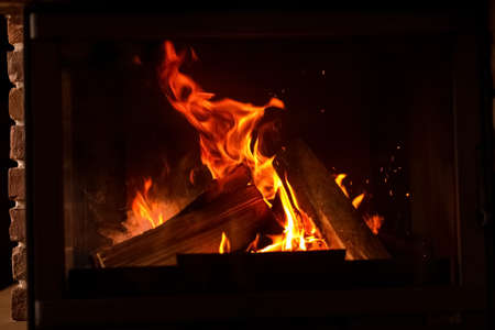 Fireplace with burning wood, closeup view. Winter vacation