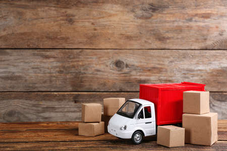 Truck model and carton boxes on wooden background, space for text. Courier service