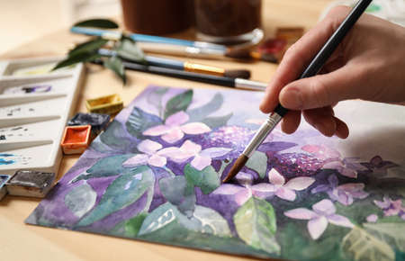 Woman painting flowers with watercolor at table, closeup