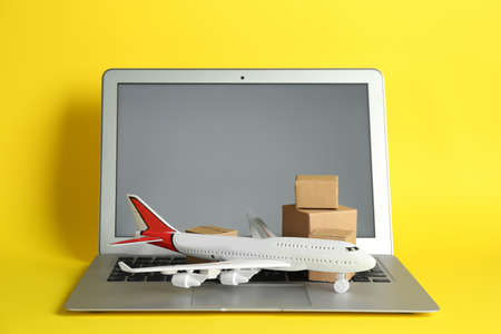 Laptop, airplane model and carton boxes on yellow background. Courier service