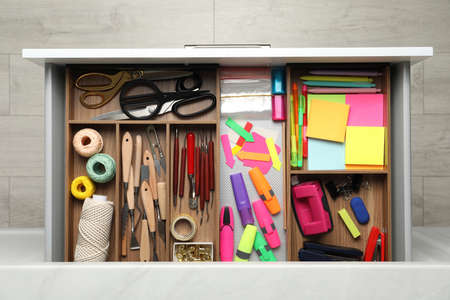 Stationery and sewing accessories in open desk drawer, top view Archivio Fotografico