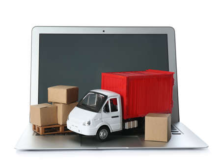 Laptop, truck model and carton boxes on white background. Courier service
