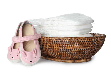 Wicker bowl with disposable diapers and child's shoes on white background