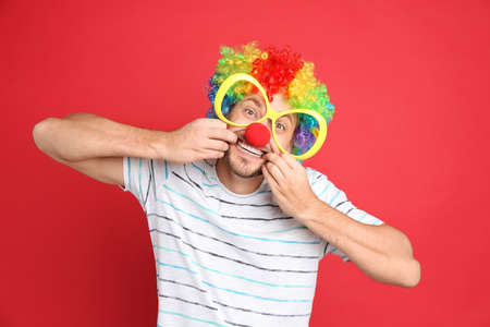 Funny man with large glasses, rainbow wig and clown nose on red background. April fool's day