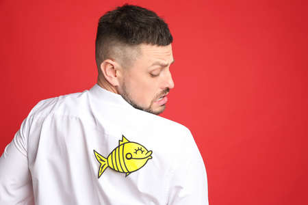 Man with paper fish on back against red background. April fool's day