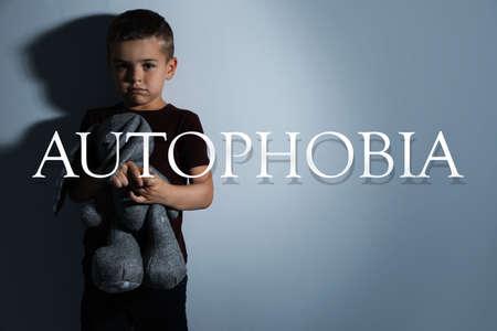 Sad little boy with toy near light wall. Autophobia 版權商用圖片