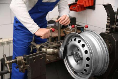 Mécanicien travaillant avec une machine de tour à disque de voiture au service des pneus, gros plan