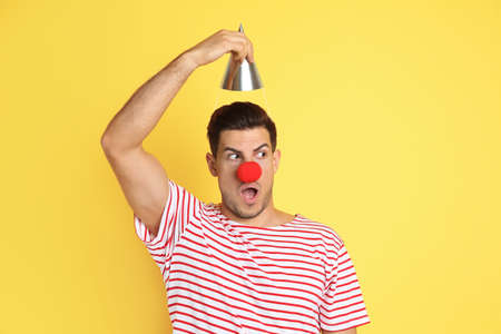 Funny man with clown nose and party hat on yellow background. April fool's day Banco de Imagens