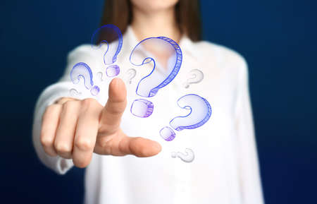 Businesswoman on blue background touching drawing of question mark