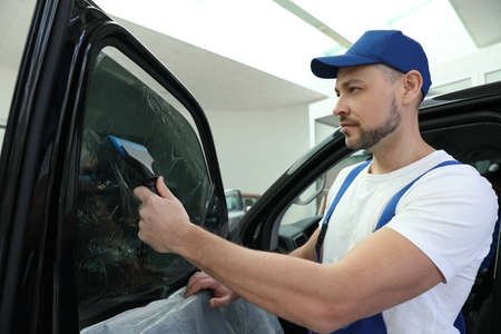 Worker tinting car window with foil in workshop Imagens
