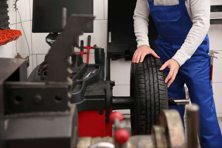 Mechanic working with wheel balancing machine at tire service, closeup