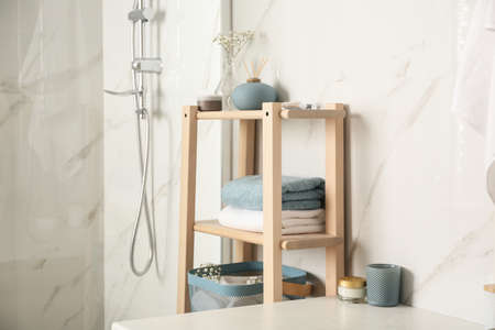 Shelving unit with clean towels in bathroom interior