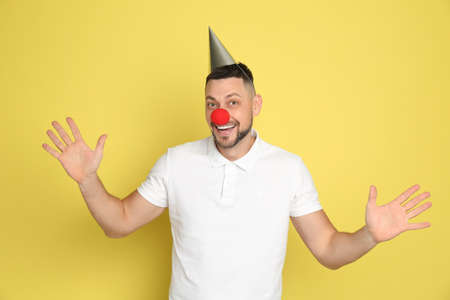 Funny man with clown nose and party hat on yellow background. April fool's day