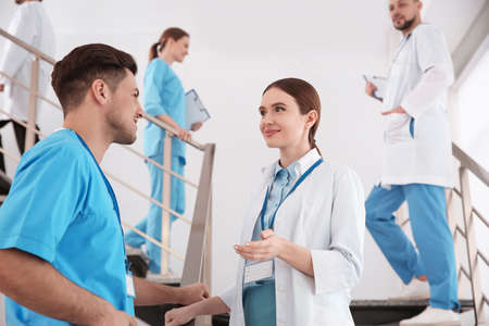 Female doctor talking to colleague on staircase in clinic