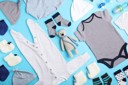 Flat lay composition with child's clothes and toy bear on light blue background