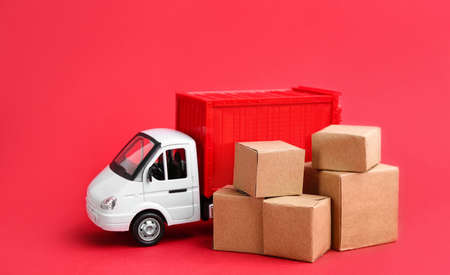 Truck model and carton boxes on red background. Courier service