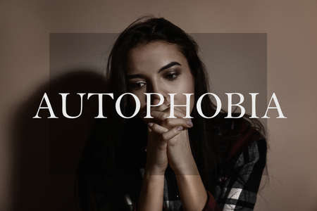 Depressed young woman near brown wall. Autophobia