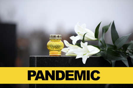 White lilies and candle on black granite tombstone outdoors. Outbreak of pandemic disease 스톡 콘텐츠