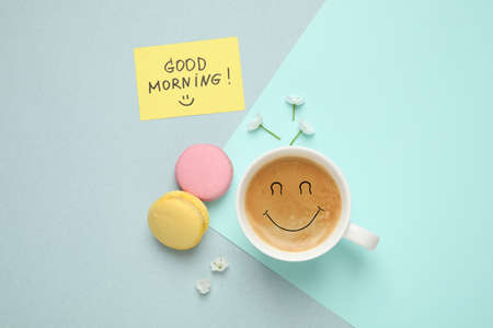 Delicious coffee, macarons, flowers and card with GOOD MORNING wish on color background, flat lay