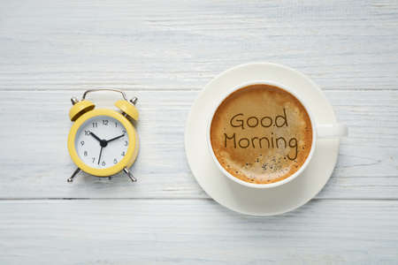 Cup of aromatic coffee and alarm clock on white wooden table, flat lay. Good morning