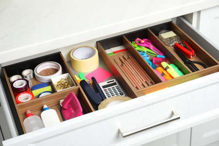 Different stationery in open desk drawer indoors Archivio Fotografico