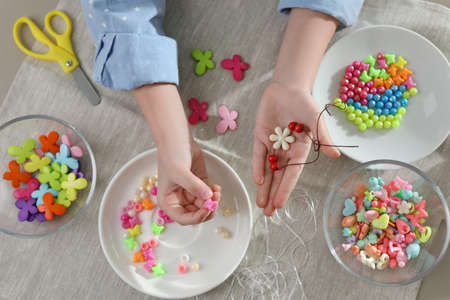 Little girl making accessory with beads at table, top view. Creative hobby