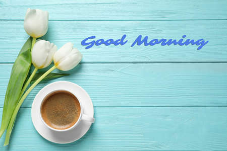 White tulips and coffee on light blue wooden table, flat lay with space for text. Good morning