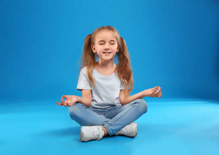 Cute little girl posing on blue background