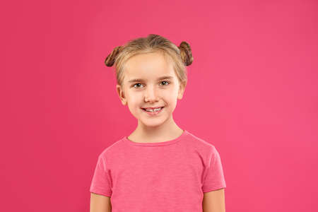 Cute little girl posing on pink background