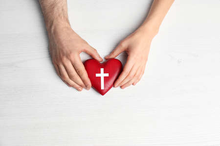 Couple holding heart with cross symbol on white wooden background, top view. Christian religion
