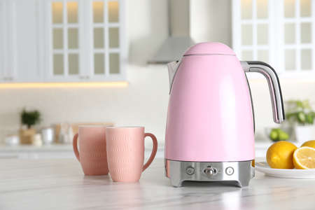 Modern electric kettle, cups and lemons on table in kitchen