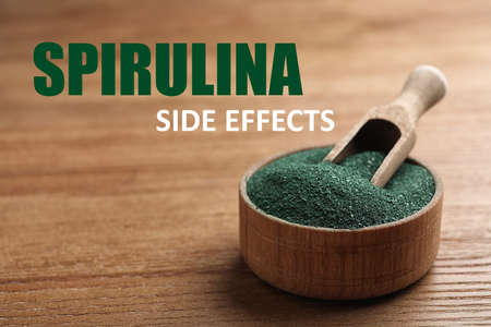 Scoop in bowl of spirulina powder on wooden table. Side effects