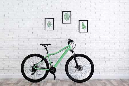 Modern green bicycle near white brick wall indoors