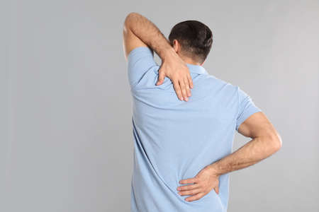 Man suffering from pain in back on light grey background. Visiting orthopedist
