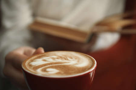 Woman with coffee reading book indoors, focus on cup Stock Photo