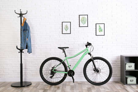 Modern green bicycle near white brick wall in stylish room interior