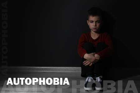 Sad little boy sitting alone near black wall, space for text. Autophobia