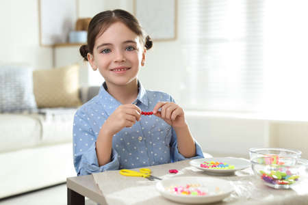 Little girl making accessory with beads at table indoors. Creative hobby Stock Photo