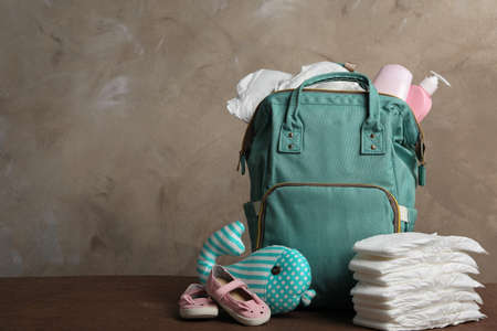 Bag with diapers and baby accessories on wooden table. Space for text