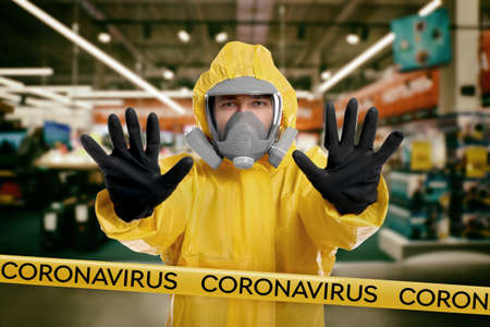 Man in chemical protective suit showing STOP gesture indoors. Prevention of virus spread Фото со стока