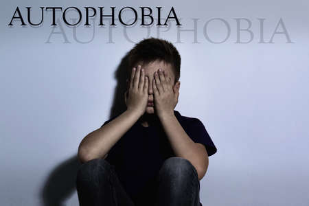 Upset boy closing eyes near white wall. Autophobia